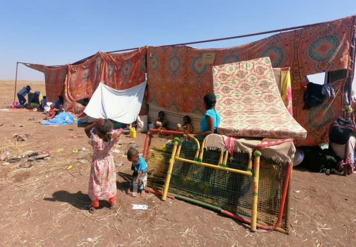 Ethiopians who fled the ongoing fighting in Tigray region, sit with their belongings in Hamdait village on the Sudan-Ethiopia border in eastern Kassala state