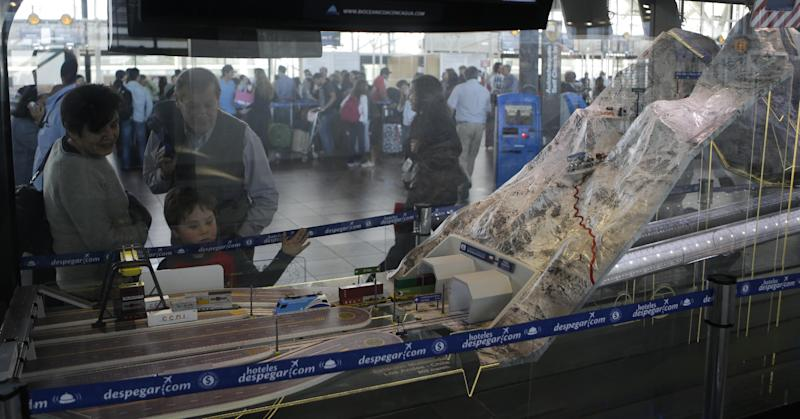 In this Sept. 12, 2012 photo, a child looks at a model train emerging from a tunnel inside a miniature model of the proposed Aconcagua Bi-Oceanico Corridor, on display at the airport in Santiago, Chile. Two of South America's leading economies are neighbors but might as well be worlds apart, separated by a mountain wall with only one major land crossing that gets snowed in for up to two months every winter. An ambitious effort to build a private railway under Andean peaks aims to end the bottleneck. (AP Photo/Eduardo Di Baia)