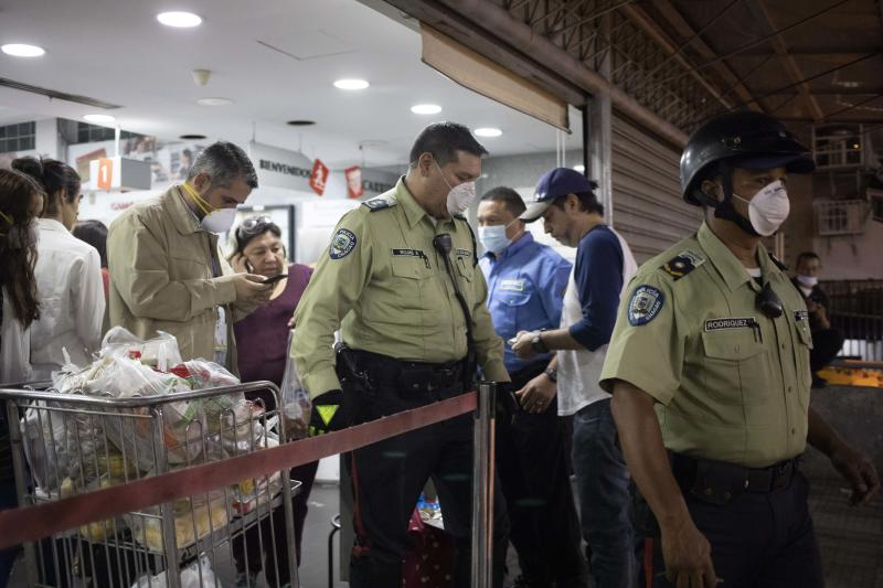CORRECTS DAY - Police officers leave a supermarket after ordering it closed after finding costumers not wearing surgical masks to cover mouth and nose in Caracas, Venezuela, Sunday, March 15, 2020. Venezuelan President Nicolás Maduro has ordered residents in the capital of Caracas and six states to stay home under a quarantine bid to control the spread of the coronavirus. (AP Photo/Ariana Cubillos)