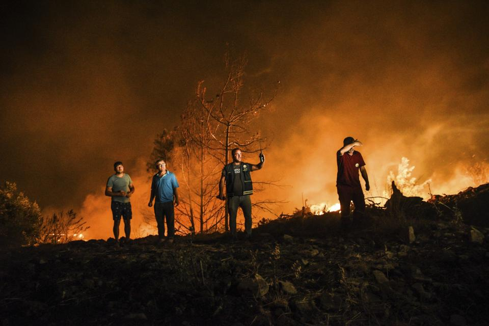 Firefighters and local villagers respond to a fire in Kirli village near the town of Manavgat, in Antalya province, Turkey, early Friday July 30, 2021. The fire that continued all night could not be brought under control and people living in the village started to evacuate. Wildfires are common in Turkey's Mediterranean and Aegean regions during the arid summer months, although some previous forest fires have been blamed on arson. (AP Photo)