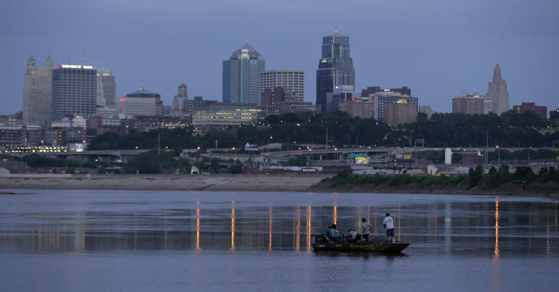FILE - In this Sunday, June 23, 2013, file photo, people fish in the Missouri River along the banks of downtown Kansas City, Mo. Amazon's final cut of 20 contenders for its second headquarters leaves hundreds of cities disappointed. That includes hopefuls like Detroit, Memphis, Tenn., and Kansas City, Mo. (AP Photo/Charlie Riedel, File)