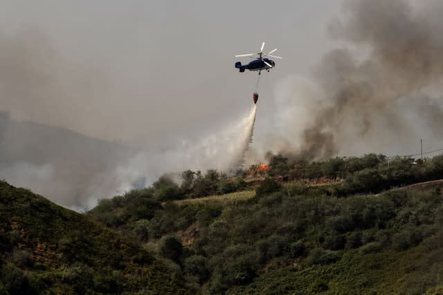 A helicopter operates over the Gran Canaria wildfire