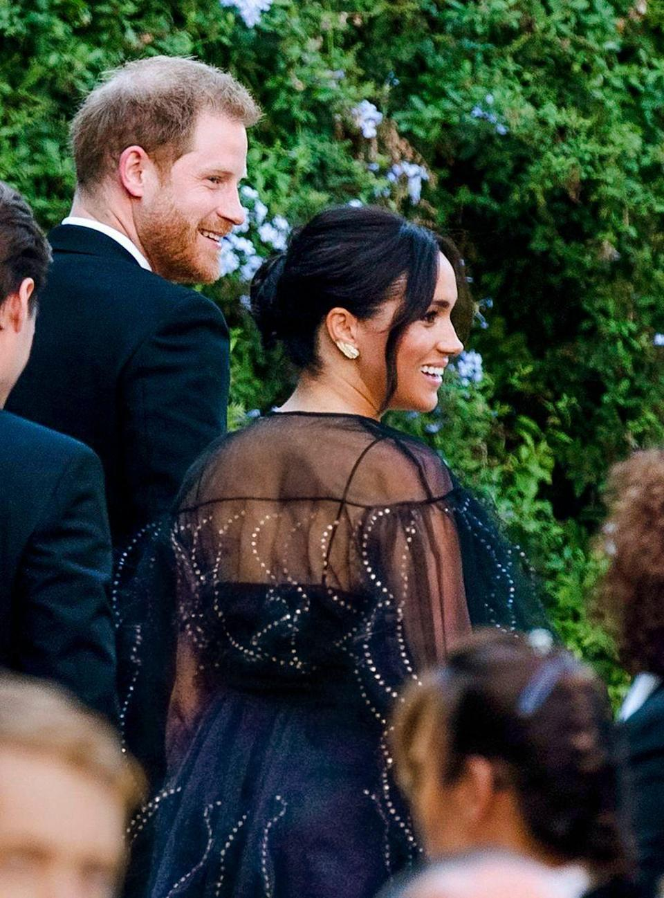 <p>The Duchess of Sussex attended the nuptials of Misha Nonoo (who was rumored to have set her up with her husband Prince Harry) and Mikey Hess in Rome wearing a striking black chiffon dress with metallic embellishment on the whimsical pleats. </p>