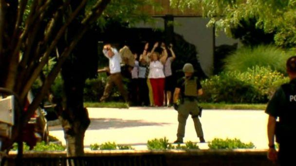 PHOTO: People walk out of a building with their hands up in Annapolis, Md., after reports of a shooting, June 28, 2018. (WJLA)