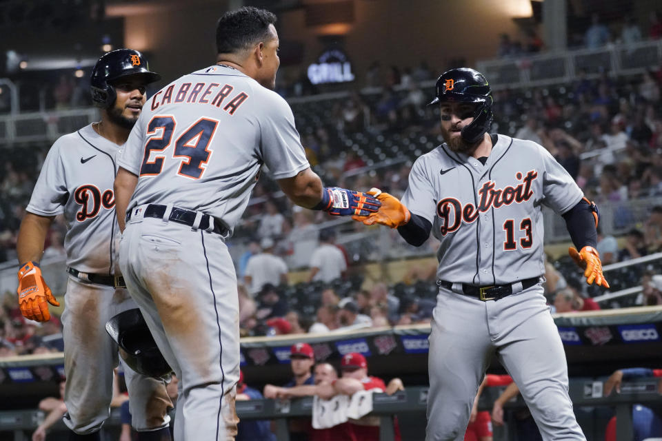 Detroit Tigers' Eric Haase (13) is congratulated by Miguel Cabrera after hitting a grand slam off Minnesota Twins pitcher Hansel Robles during the ninth inning of a baseball game Tuesday, July 27, 2021, in Minneapolis. The Tigers won 6-5 in 11 innings. (AP Photo/Jim Mone)