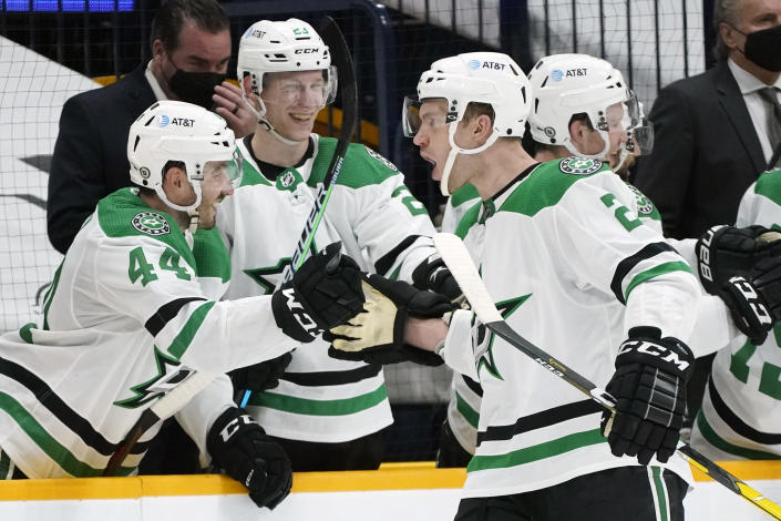 Dallas Stars defenseman Jamie Oleksiak (2) is congratulated by Joel Hanley (44) and Esa Lindell (23) after scoring a goal against the Nashville Predators in the second period of an NHL hockey game Sunday, April 11, 2021, in Nashville, Tenn. (AP Photo/Mark Humphrey)