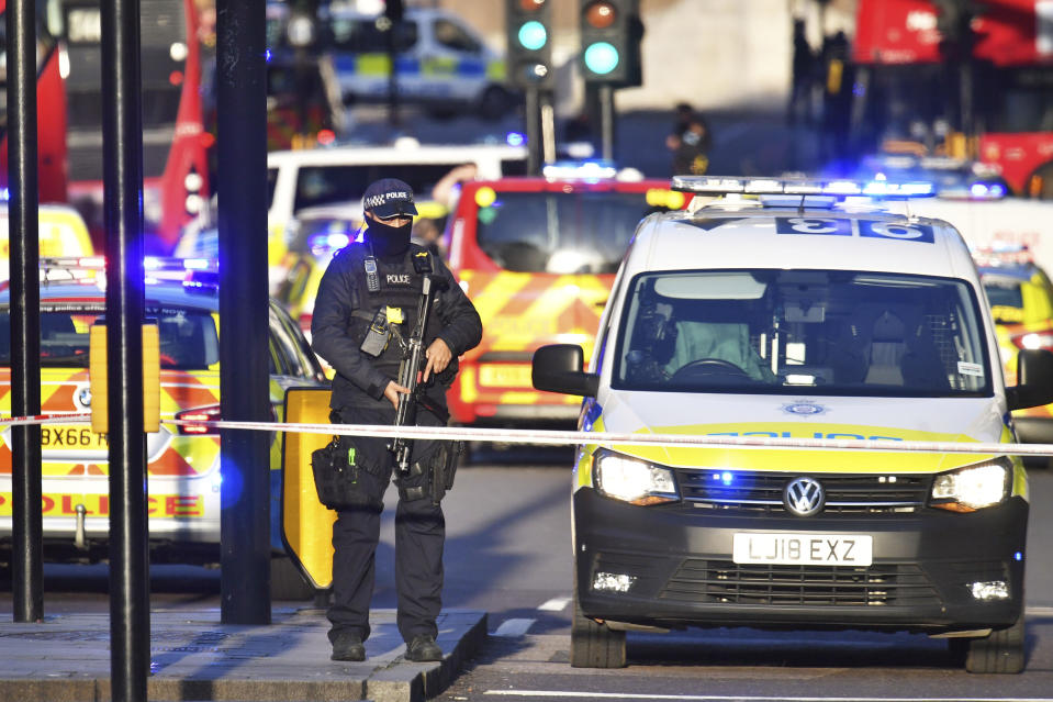 """Armed police at the scene of an incident on London Bridge in central London following a police incident, Friday, Nov. 29, 2019. British police said Friday they were dealing with an incident on London Bridge, and witnesses have reported hearing gunshots.  The Metropolitan Police force tweeted that officers were """"in the early stages of dealing with an incident at London Bridge."""" (Dominic Lipinski/PA via AP)"""