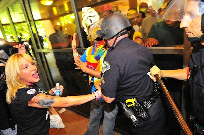 Demonstrators gather on the steps of Anaheim City Hall Tuesday afternoon July 25, 2012, to protest the death of Manuel Diaz, 25, who died as a result of gunshot wounds sustained during a police pursuit by the Anaheim Police Department last Saturday on North Anna Drive. Riot police fired bean bag rounds and pepper balls into a crowd of protestors late Tuesday outside City Hall. (AP Photo/The Orange County Register,Stuart Palley ) MAGS OUT; LOS ANGELES TIMES OUT