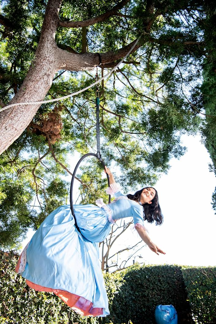 Rose, in a baby blue gown, sits on an aerial hoop, leaning back and hanging on with one hand.