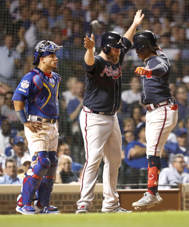 Atlanta Braves' Brian McCann, center, greets Ozzie Albies, right, at home after the pair scored on Albies' two-run home run as Chicago Cubs catcher Willson Contreras watches during the seventh inning of a baseball game, Tuesday, June 25, 2019, in Chicago. (AP Photo/Charles Rex Arbogast)