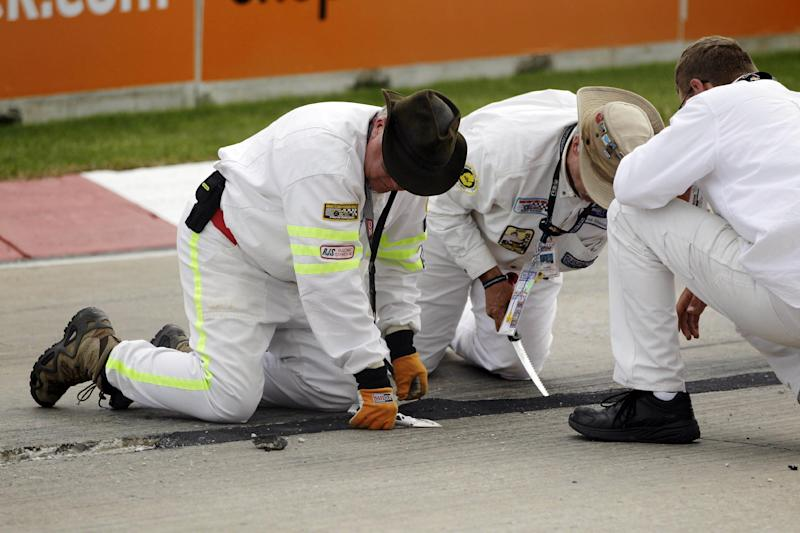 Crew members look over the asphalt patch on the road course during IndyCar's Detroit Grand Prix auto race on Belle Isle in Detroit, Sunday, June 3, 2012. The race was red flagged 63 minutes into the race because of the road condition. (AP Photo/Carlos Osorio)