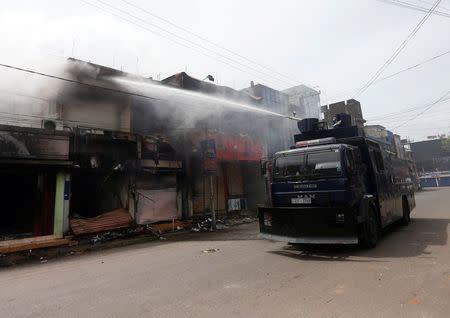 A police vehicle sprays water from a water cannon on a burnt shop after a clash between Buddhists and Muslims in Aluthgama