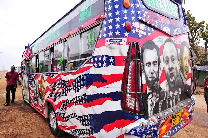 """Minibus driver Solomon Murimia calls on clients next to his """"matatu"""" minibus with a painting depicting US Presidents Abraham Lincoln and Barack Obama and US civil rights leader Martin Luther King on July 22, 2015 in Nairobi (AFP Photo/Simon Maina)"""