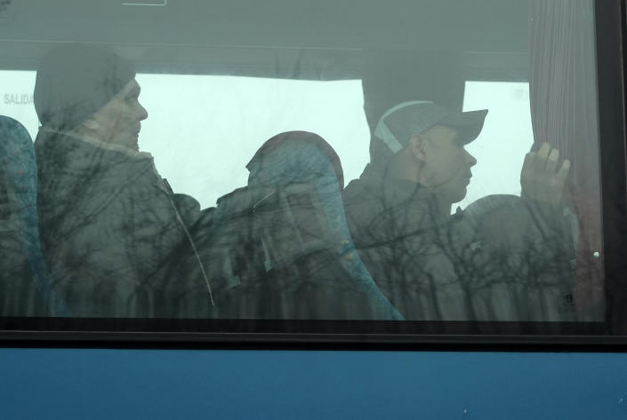 Russia-backed war prisoners are seen through a bus window, driving to be exchanged near Odradivka, eastern Ukraine, Sunday, Dec. 29, 2019. Ukrainian forces and Russia-backed rebels in the east have begun exchanging prisoners in a move aimed at ending their five-year-long war. (AP Photo/Evgeniy Maloletka)
