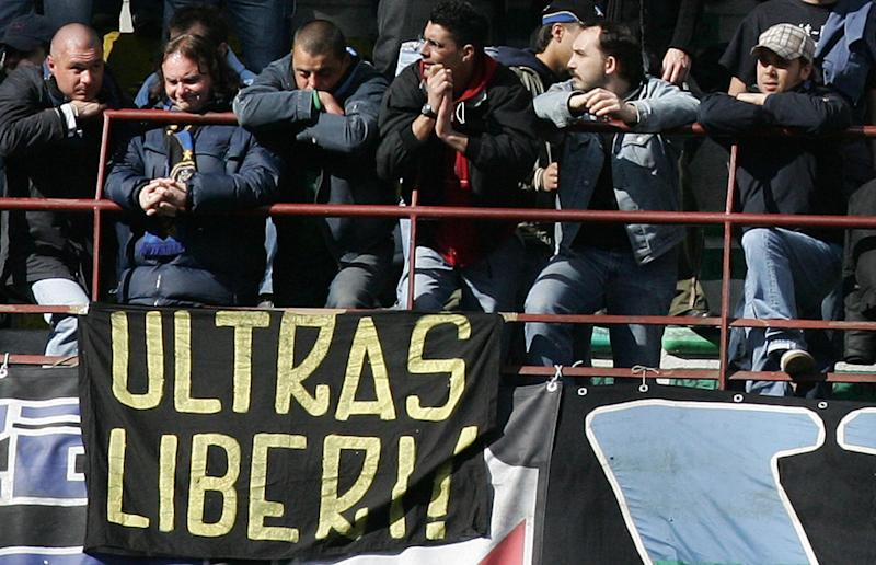 "MILAN, Italy: Inter Milan's fans sit by a flag reading ""Ultra Free"" during the serie A football match Inter Milan-Cagliari at San Siro stadium in Milan, 17 April 2005. European football's governing body UEFA handed Inter Milan a six-match stadium ban on Friday after their quarter-final with AC Milan was abandoned when Inter fans threw flares on to the pitch. AFP PHOTO / Paco SERINELLI (Photo credit should read PACO SERINELLI/AFP/Getty Images)"