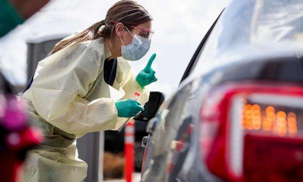 PHOTO: Ashley Layton, an LPN at St. Luke's Meridian Medical Center, communicates with a person exhibiting symptoms before taking swab sample at a special outdoor drive-thru screening station for coronavirus COVID-19 Tuesday, March 17, 2020. (Darin Oswald/Idaho Statesman/Tribune News Service via Getty Images)