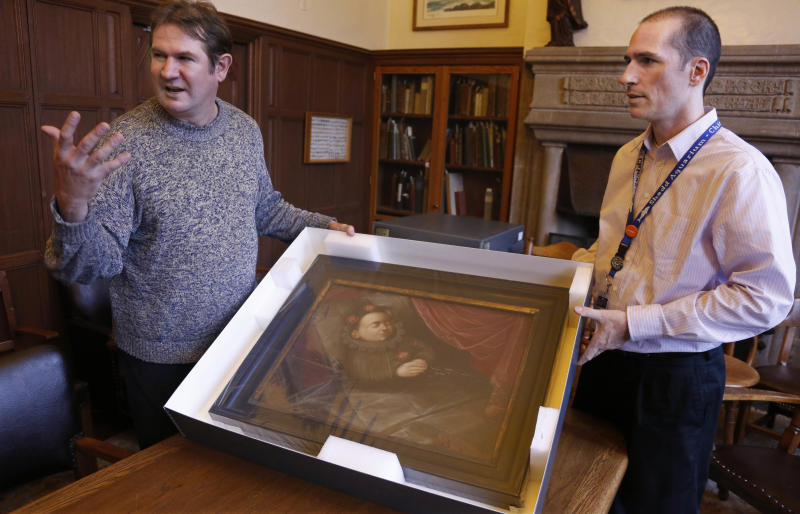 """In this Oct. 29, 2013, photo taken in Evanston, Ill., Scott Krafft, left, curator of the Charles Deering McCormick Library of Special Collections, and manuscript librarian Benn Joseph display a painting of a dead Spanish boy from the 1,600s. The portrait is one of the artifacts from the """"Death Collection""""- an archive of death-related oddities once owned by horror novelist and screenwriter Michael McEachern McDowell that have been purchased by Northwestern University. (AP Photo/M. Spencer Green)"""