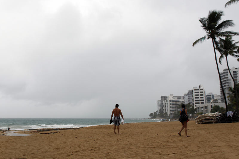 A couple walks on a beach as hurricane Irma approaches Puerto Rico in San Juan, on Sept. 5.