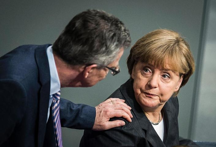 """German Interior Minister Thomas de Maiziere -- who denies charges of misleading lawmakers over the """"BND affair"""" -- speaks with Chancellor Angela Merkel at the Bundestag in Berlin, on January 15, 2015 (AFP Photo/Odd Andersen)"""