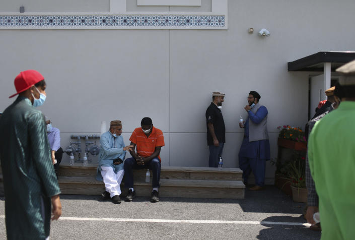 Community members talk outside of their local mosque in Rosedale, Md., after Friday prayer on Aug. 13, 2021. (AP Photo/Jessie Wardarski)