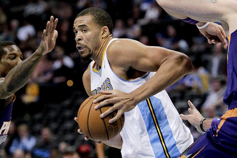 Denver Nuggets' JaVale McGee, center, works through Phoenix Suns' defenders during the first quarter of an NBA basketball preseason game on Wednesday, Oct. 23, 2013, in Denver. (AP Photo/Barry Gutierrez)
