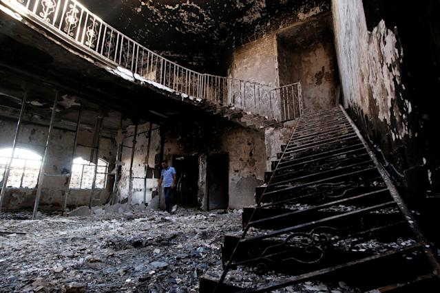 <p>Men are seen inside the headquarters of Asaib Ahl al-Haq, set on fire by protesters yesterday, in Basra, Iraq, Sept. 7, 2018. (Photo: Essam al-Sudani/Reuters) </p>