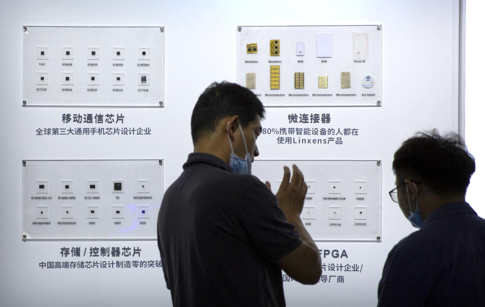 People look at semiconductors on display from the Tsinghua Unigroup at the China Beijing International High Tech Expo in Beijing, Saturday, Sept. 19, 2020. Chinese leaders are shifting focus from the coronavirus back to long-term goals of making China a technology leader at this year's highest-profile political event, the meeting of its ceremonial legislature, amid tension with Washington and Europe over trade, Hong Kong and human rights. (AP Photo/Mark Schiefelbein)