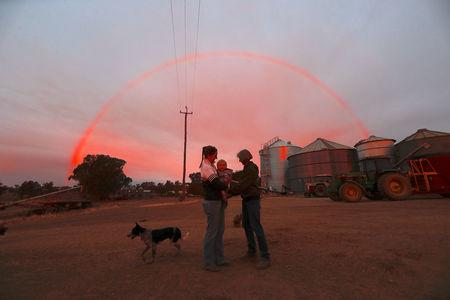 Farmer Tom Wollaston's wife Margo talks with her daughter Natasha and her granddaughter Abbey as a rainbow forms above them at sunset on their drought-effected property, located west of the town of Tamworth, in north-western New South Wales in Australia, June 2, 2018. Picture taken June 2, 2018.    REUTERS/David Gray