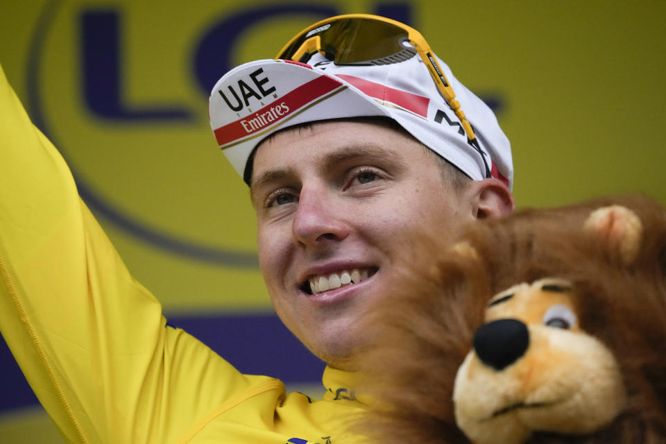 Slovenia's Tadej Pogacar, wearing the overall leader's yellow jersey, celebrates on the podium after the eighth stage of the Tour de France cycling race over 150.8 kilometers (93.7 miles) with start in Oyonnax and finish in Le Grand-Bornand, France,Saturday, July 3, 2021. (AP Photo/Christophe Ena)