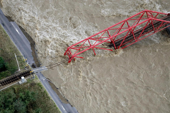 A collapsed railway bridge is seen over the Chikuma river swollen by Typhoon Hagibis in Ueda, Nagano prefecture, central Japan, Sunday, Oct. 13, 2019. Rescue efforts for people stranded in flooded areas are in full force after a powerful typhoon dashed heavy rainfall and winds through a widespread area of Japan, including Tokyo.(Kyodo News via AP)