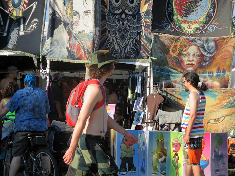 In this Friday, July 26 photo released by Paul Duning, a music fan at the Gathering of the Vibes festival walks by a vendor selling souvenirs including one with the image of the late Jerry Garcia, the Grateful Dead guitarist who died in 1995. The festival draws about 20,000 fans to this small city on the Connecticut coast and features a wide variety of bands including offshoots of the Grateful Dead. (AP Photo/Paul Duning)