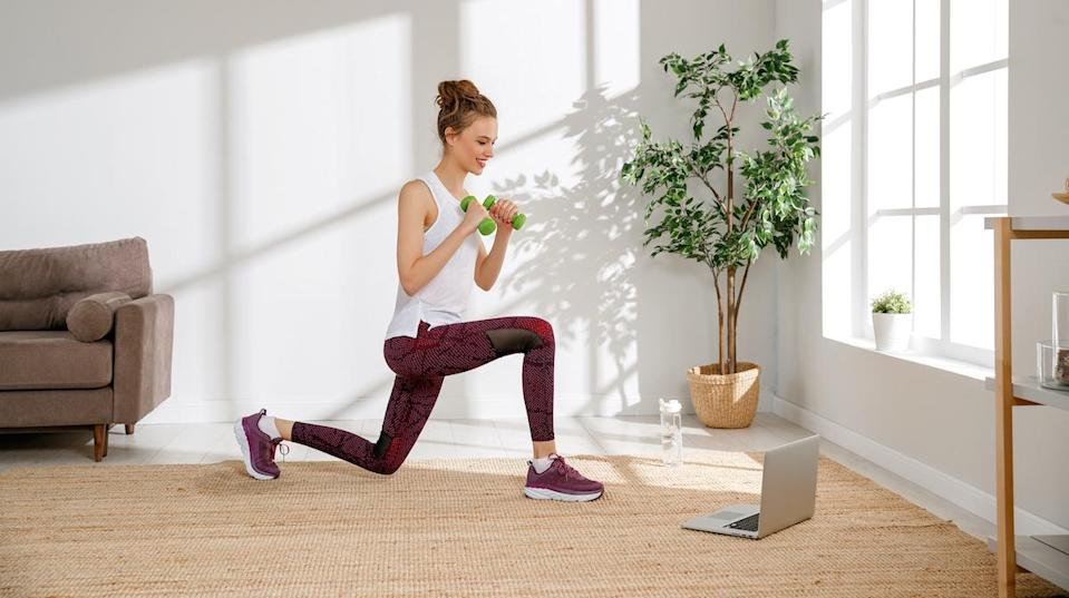 Side view of active young female in sportswear doing exercises lunges with dumbbells and watching video on laptop during fitness workout at home