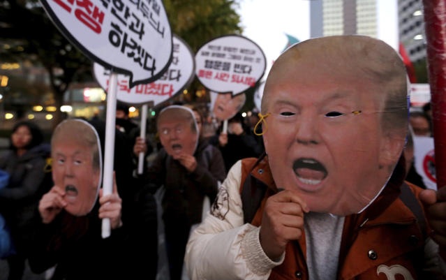 "<p>Protesters wearing masks of President Donald Trump march toward the U.S. Embassy during a rally to oppose a planned his visit in Seoul, South Korea, Saturday, Nov. 4, 2017. The signs read "" Stop the War."" (Photo: Ahn Young-joon/AP) </p>"