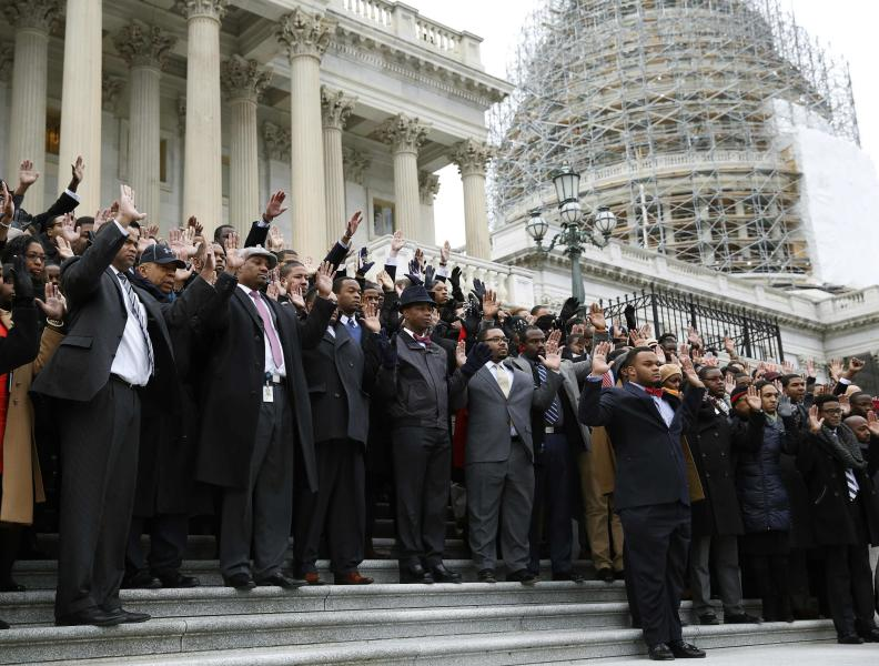 """African-American Congressional staffers and representatives stage a walk out with a """"Hands Up, Don't Shoot"""" pose on the steps of the House of Representatives at the U.S. Capitol to protest the deaths of Michael Brown and Eric Garner, in Washington December 11, 2014. REUTERS/Gary Cameron   (UNITED STATES - Tags: CRIME LAW POLITICS CIVIL UNREST)"""