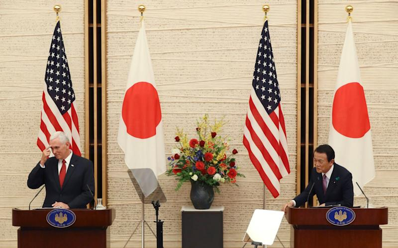 US Vice President Mike Pence, left, and Japanese Deputy Prime Minister and Finance Minister Taro Aso listen to a question from a reporter during their joint press conference at the prime minister's office in Tokyo, - Credit: AP