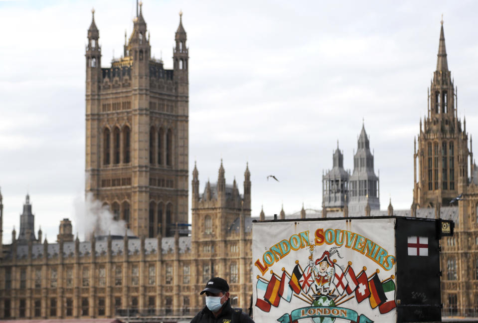 A man walks past a souvenir shop opposite the Houses of Parliament during the debate in the House of Commons on the EU (Future Relationship) Bill in London, Wednesday, Dec. 30, 2020. The European Union's top officials have formally signed the post-Brexit trade deal with the United Kingdom, as lawmakers in London get set to vote on the agreement. (AP Photo/Frank Augstein)