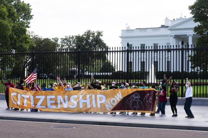 Protesters risk arrest as they rally on the sidewalk by the White House on Pennsylvania Avenue, Thursday, Oct. 7, 2021, in Washington. The protesters urged Vice President Kamala Harris and Senate Democrats to include immigration reform in the reconciliation package. (AP Photo/Jacquelyn Martin)