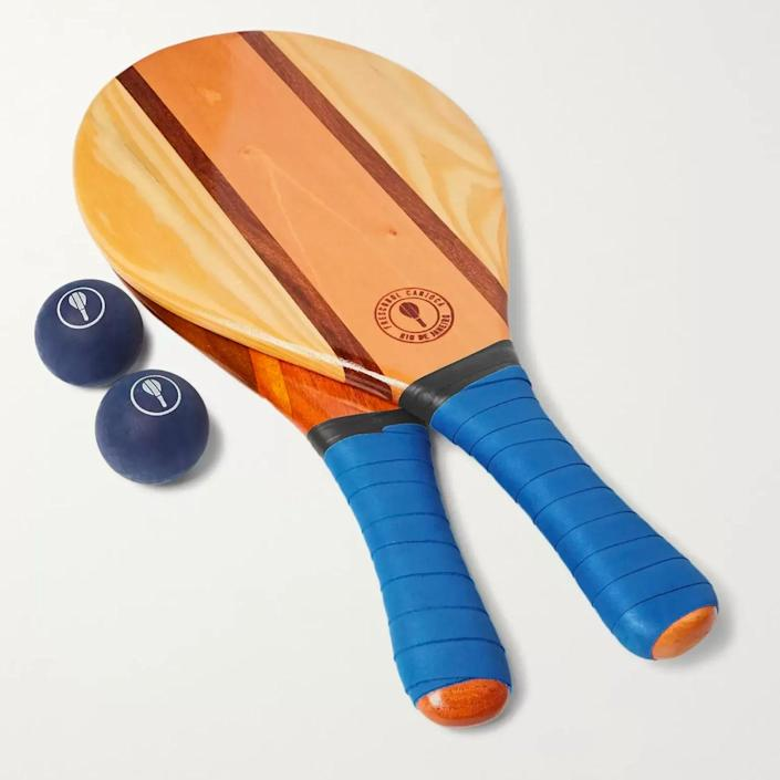 """Yes, $260 for a beach bat and two balls is a lot. But hear us out: This set is handmade and therefore worthy of becoming an heirloom. (Just saying!) $260, Mr Porter. <a href=""""https://www.mrporter.com/en-us/mens/product/frescobol-carioca/lifestyle/leisure-games/trancoso-wooden-beach-bat-and-ball-set/3024088872970011"""" rel=""""nofollow noopener"""" target=""""_blank"""" data-ylk=""""slk:Get it now!"""" class=""""link rapid-noclick-resp"""">Get it now!</a>"""