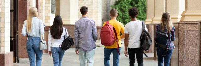 Group of students walking on college campus after classes, back view.