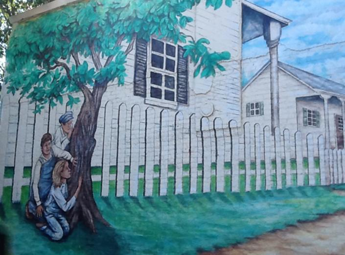 """A hand-painted mural showing a scene of the 1960 bestseller """" To Kill A Mockingbird"""" is shown on a building near where the homes of 1960's writers Harper Lee and Truman Capote's homes once stood in Monroeville, Alabama October 23, 2013. Lee, the 87-year-old author of the still-popular 1960 bestseller, recently filed a lawsuit against the museum dedicated to her novel in a dispute over a merchandising trademark. Photo taken October 23, 2013. REUTERS/Verna Gates (UNITED STATES - Tags: SOCIETY)"""