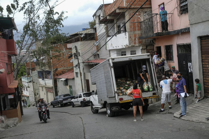 Residents help to unload bags of basic food staples, such as pasta, sugar, flour and kitchen oil, provided by a government food assistance program, as a couple on a motorcycle drive past in front of they in the Santa Rosalia neighborhood of Caracas, Venezuela, Saturday, April 10, 2021. The program known as Local Committees of Supply and Production, CLAP, provides subsidized food for vulnerable families, especially now in the midst of a quarantine to stop the COVID-19 pandemic that has left many without income. (AP Photo/Matias Delacroix)