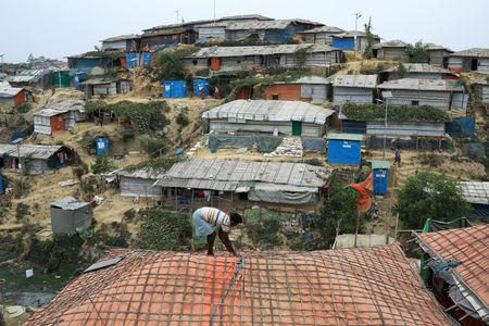 FILE PHOTO: A Rohingya refugee repairs the roof of his shelter at the Balukhali refugee camp in Cox's Bazar