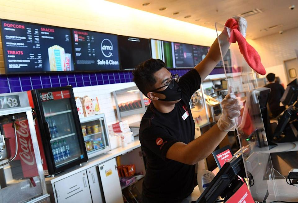 <p>Zach Fontana sanitizes a plexiglass safety shield divider at the concession stand at AMC Town Square 18 on August 20 in Las Vegas, Nevada.</p>