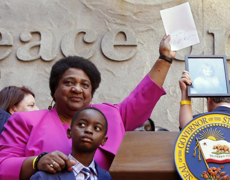 Assemblywoman Shirley Weber, D-San Diego, holds up her measure signed by Gov. Gavin Newsom that limits the use of lethal force by law enforcement Sacramento, Calif., Monday, Aug. 19, 2019. Weber's bill, AB392, would bar police from using lethal force unless it is necessary to prevent imminent threat of death or serious injury to themselves and others. (AP Photo/Rich Pedroncelli)