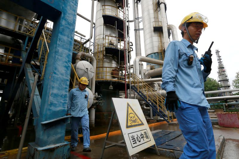 FILE PHOTO: Technicians walk down the refinery which produces ethanol gasoline for vehicles, at China's Petroleum and Chemical Corporation, or Sinopec, Tianjin company in Tianjin