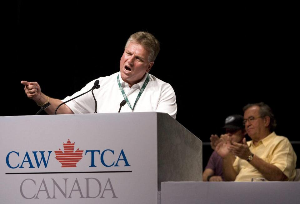 Ken Lewenza gestures while standing behind a dias that has the CAW logo.
