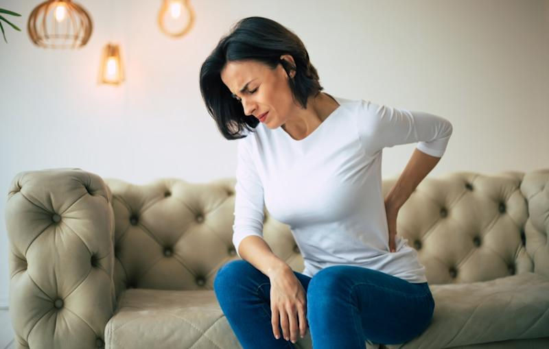 Woman holds her belly with hands with closed eyes due to pain