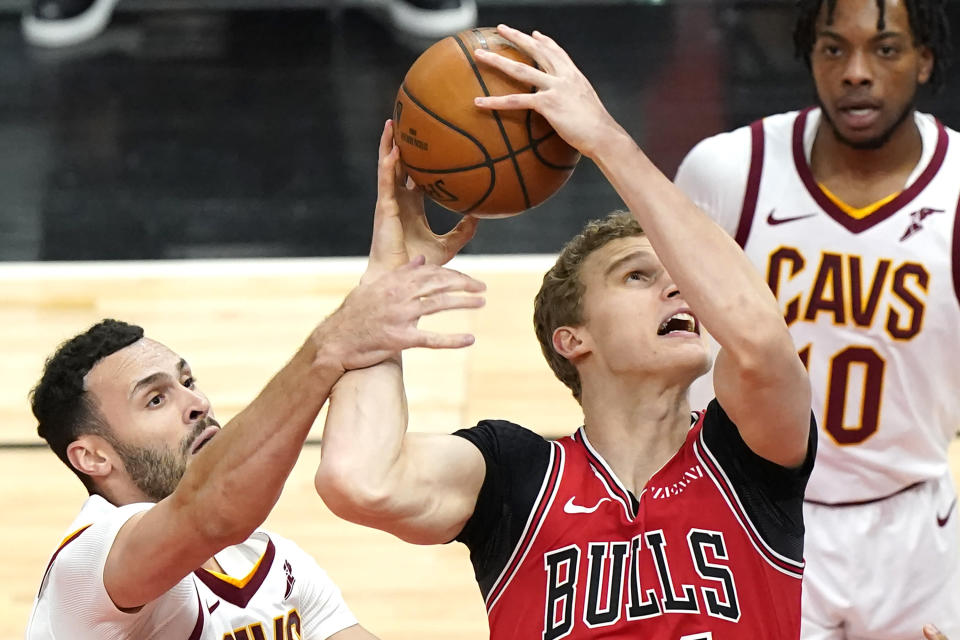 Chicago Bulls forward Lauri Markkanen, center, shoots against Cleveland Cavaliers forward Larry Nance Jr., left, as Cleveland Cavaliers guard Darius Garland, right, watches during the first half of an NBA basketball game in Chicago, Wednesday, March 24, 2021. (AP Photo/Nam Y. Huh)