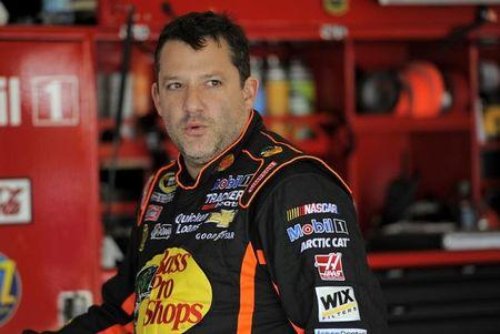 NASCAR Sprint Cup Series driver Tony Stewart, of the number 14 car, speaks with crew members in the garage during practice for the Daytona 500 qualifying at Daytona International Speedway in Daytona Beach
