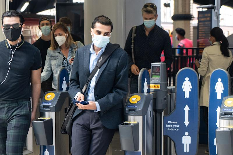 Commuters wearing face masks walk through the ticket barriers at Waterloo Station in London on June 15, 2020 after new rules make wearing face coverings on public transport compulsory while the UK further eases its coronavirus lockdown. - New coronavirus pandemic rules coming into force on June 15 make wearing face coverings such as masks or scarves compulsory on public transport, as various stores and outdoor attractions open for the first time in nearly three months. (Photo by Niklas HALLE'N / AFP) (Photo by NIKLAS HALLE'N/AFP via Getty Images)